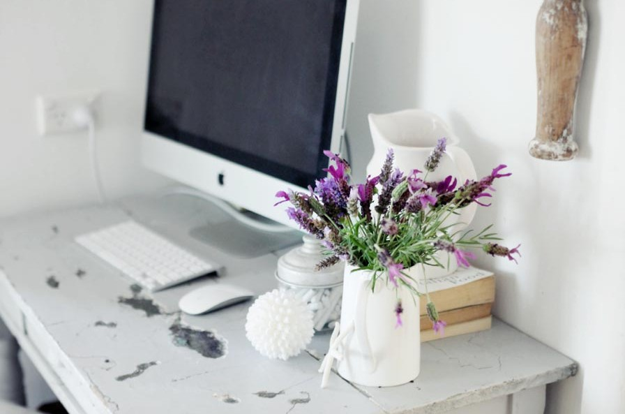 Desktop computer with flower vase.